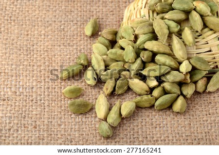 Green Cardamom pods on sack cloth - stock photo