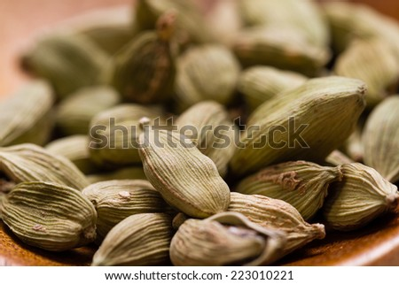 Green Cardamom Pods on wooden background closeup  - stock photo