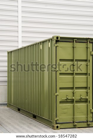 green cargo container in front of a wall - stock photo