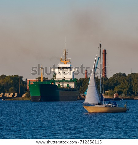 Green cargo ship leaves the port in a clear day