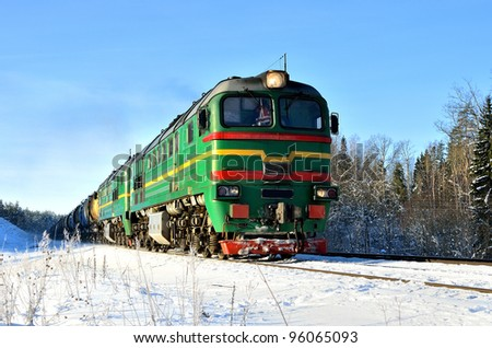 green cargo train on the move in winter - stock photo