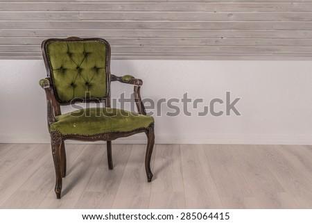 Green chair in victorian design on wooden floor - stock photo