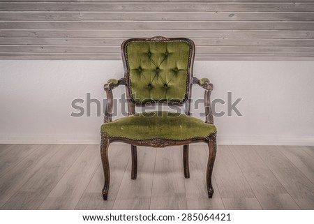 Green chair in victorian style on wooden floor - stock photo