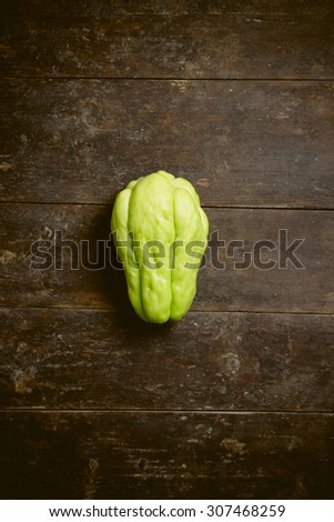 Green chayote is on the old wooden background. - stock photo