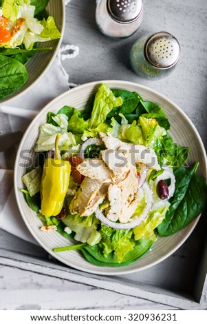 Green chicken salad on wooden background