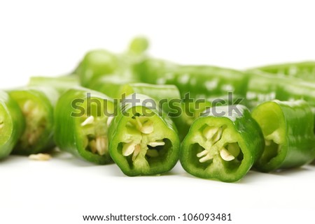 Green chili pepper cut in pieces on a white background - stock photo