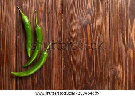 Green chili peppers on wooden table with copy space - stock photo