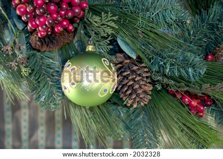 Green christmas ball hanging on a tree with pine-cones and berries, - stock photo