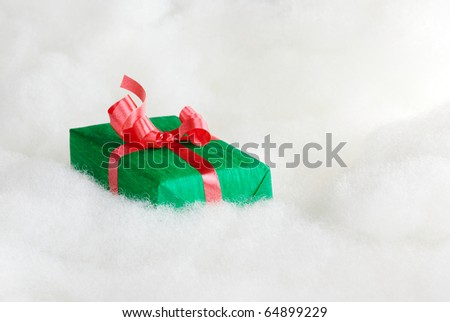Green Christmas gift with red ribbon on white cotton that looks like clouds (Selective Focus, Focus on the first half of the gift box)