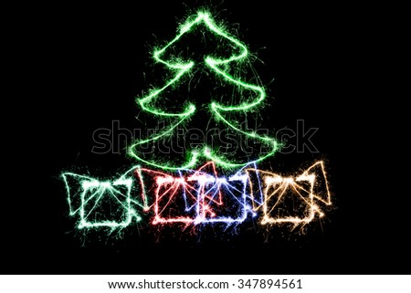Green Christmas tree and gifts made by sparkler on a black background - stock photo