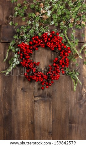 green christmas tree branches and wreath from red berries over rustic wooden background. festive decoration - stock photo