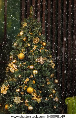 green Christmas tree decorated with Golden yellow cones ornaments near the brown wall in the dark