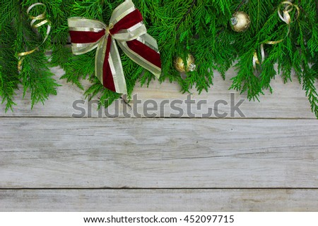 Green Christmas tree garland border with gold and red bow and ornaments on antique rustic wood background - stock photo