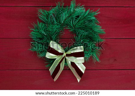Green Christmas wreath with red and gold bow hanging on dark red wooden background - stock photo