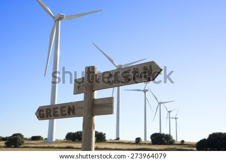Green-Clean cross road sign with windmills in the background - stock photo
