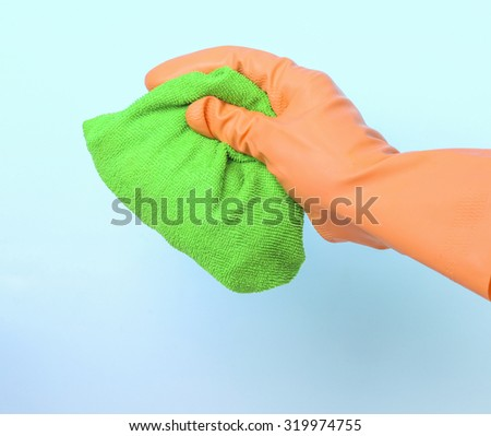 Green cleaning rag in gloved hand - stock photo