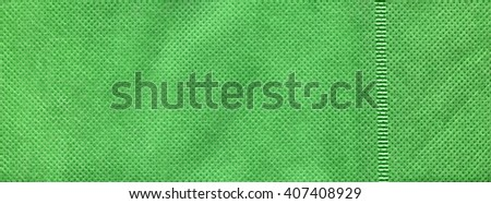 Green cloth nonwoven fabric texture background. Spunbond. Eco-banner. Fabric bright ecological canvas wallpaper with delicate striped pattern. Green towel texture rag. Green cloth texture. - stock photo