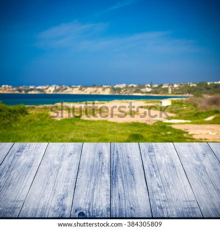 Green coastline and blue water of the Mediterranean Sea over old light wooden table or board. Blue sky like natural background. Collage. Selective Focus. Toned. - stock photo