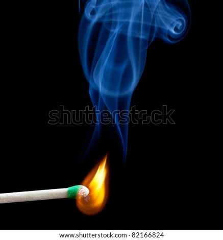 Green coated match head starts to burn with light blue smoke