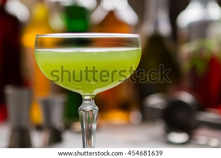 Green cocktail in glass. Coupe glass with bright liquid. Delicious drink made by bartender. Kiwi daiquiri with fresh juice.