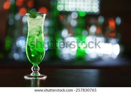 Green cocktail on table on dark background - stock photo