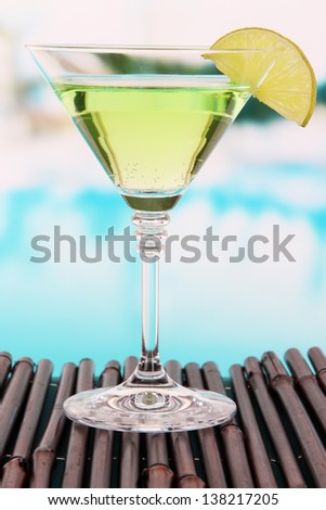 Green cocktail with lime on table on bright background - stock photo