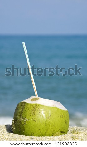 Green coconut on a tropical beach - stock photo