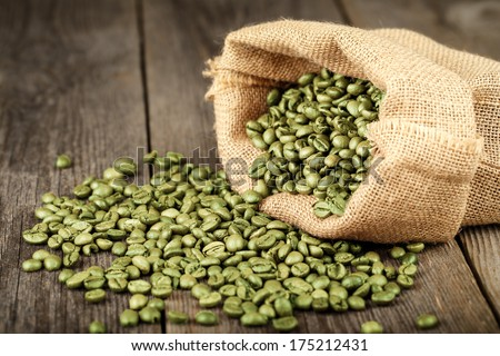 Green coffee beans in coffee bag made from burlap on wooden surface. Focused in middle of the frame. - stock photo