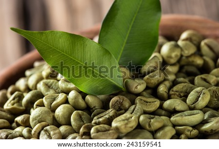 green coffee beans in wooden bowl, close-up. - stock photo