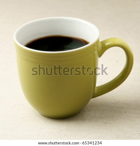 Green coffee mug on rustic table cloth - stock photo