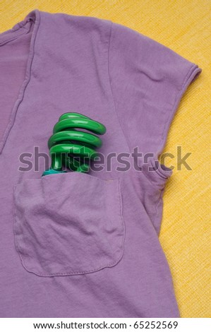 Green Compact Fluorescent Light Bulb in a Shirt Pocket on a Yellow Background.  Eco Friendly Concept.