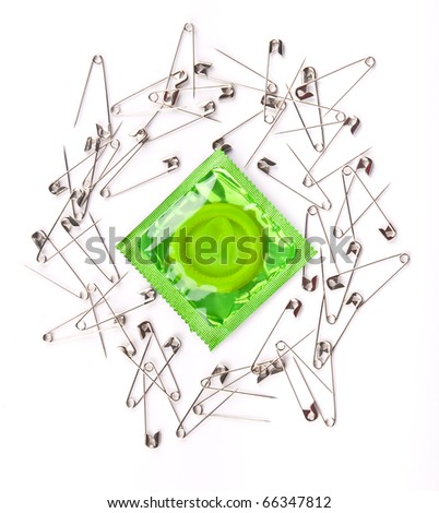 Green condom surrounded by opened metal safety pins - stock photo
