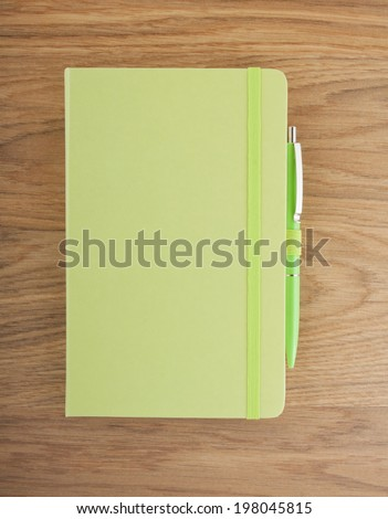Green copybook with elastic band and pen on a wooden background - stock photo