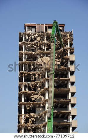 Green crane demolishing a highrise building - stock photo