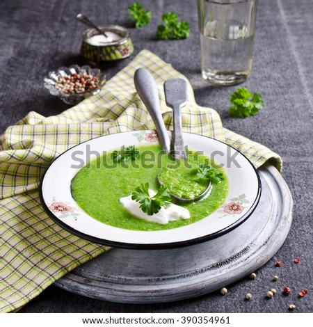 Green cream soup in a bowl on a dark background. Selective focus.