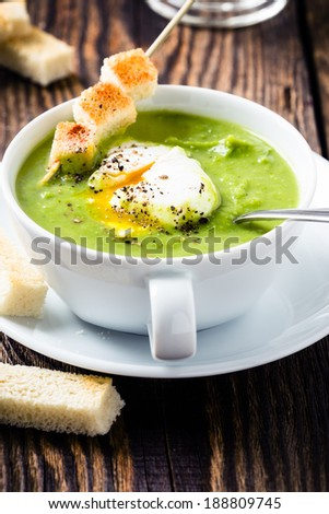 Green cream soup with poached egg and croutons - stock photo
