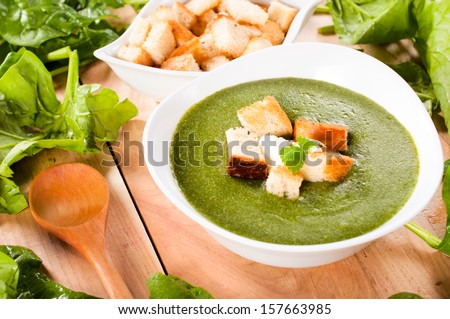 Green creamy soup with spinach. Selective focus on the dried crust in soup - stock photo