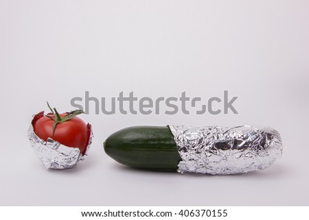 Green cucumber and red tomato wrapped in foil on a white background