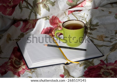 green cup of tea on the notebook pencil writing write bed reading study training linens floral print - stock photo