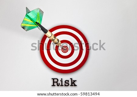 Green dart hitting a red target with a Risk label below- - stock photo