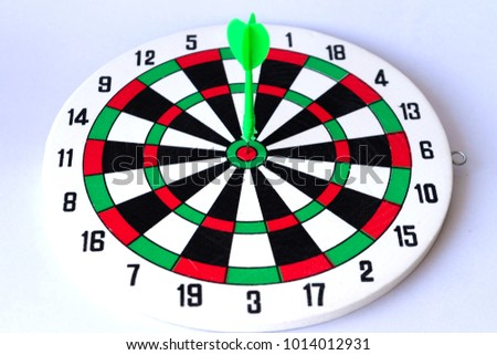 Green dart on center of dartboard isolated on white background. Smart goal setting.