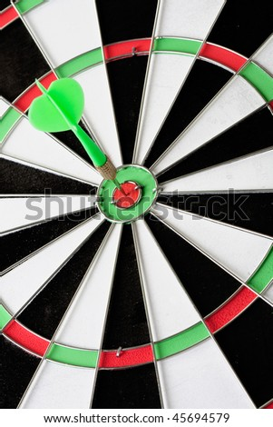 Green dart punctured in the center of the target