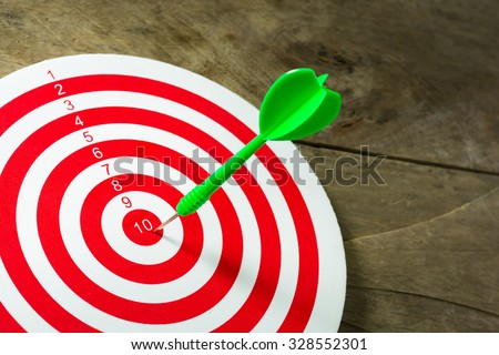 Green darts arrows in the target center on wooden background. Success hitting target aim goal achievement concept background. close up. - stock photo