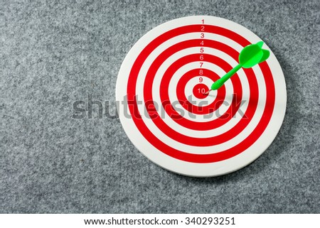 Green darts arrows in the target center. Success hitting target aim goal achievement concept background. close up. - stock photo
