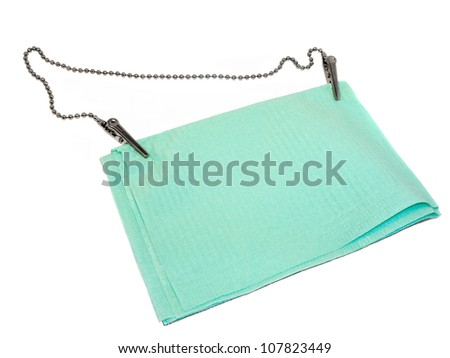 Green dental napkin with chain holder isolated on white background