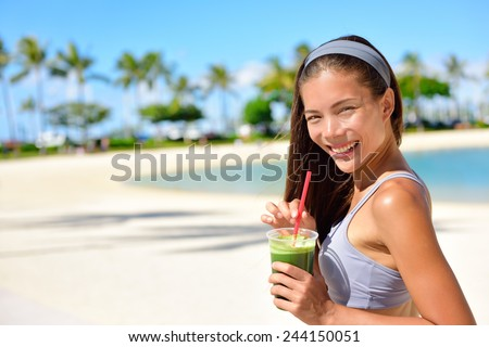 Green detox smoothie - woman drinking vegetable smoothie after fitness running workout on summer day. Fitness and healthy lifestyle concept with beautiful fit mixed race Asian Caucasian model. - stock photo