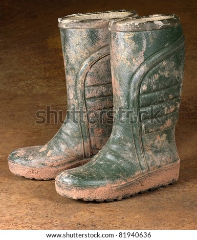 green dirty rubber boots on rusty background - stock photo