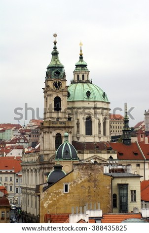 Green domes of St Nicholas Church sticking up above the red tile roof line in the Lesser Town, Prague, Czech Republic - stock photo