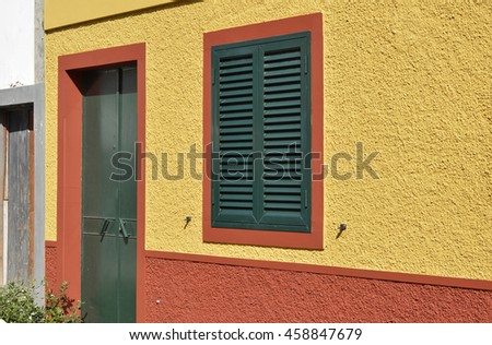 Green door and shuttered window in yellow and orange wall. Funchal, Madeira, Portugal