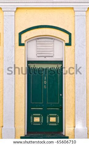 Green door between white columns on a yellow victorian building - stock photo